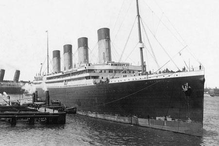 O RMS Olympic (ainda quando era RMS), ancorado numa doca em 1911*  *Nota: Se reparar o convés dos botes verá que é praticamente o mesmo do Titanic, ou seja, com dezesseis botes fixos. Dá pra ver que, a fileira de botes termina depois de quatro botes. O Olympic foi equipado com mais botes somente depois do naufrágio do Titanic, e essa foto foi tirada em 1911, ano que o Titanic foi lançado ao mar para finalizar sua construção.